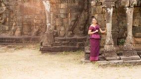Muchacha camboyana en el vestido del Khmer que se coloca en la terraza de los elefantes en la ciudad de Angkor Foto de archivo