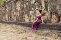 Muchacha camboyana en el vestido del Khmer que se sienta en la terraza de los elefantes en la ciudad de Angkor Foto de archivo