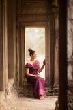 Muchacha camboyana en el vestido del Khmer que se sienta en una ventana en Angkor Wat Fotografía de archivo