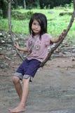 Muchacha camboyana en un oscilación del árbol Fotos de archivo