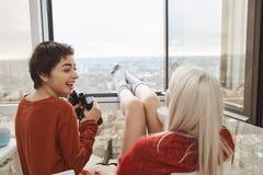 Muchacha camisa-cabelluda atractiva con risas y miradas binoculares en su novia mientras que se sienta en balcón y el goce Foto de archivo libre de regalías