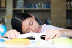 Muchacha cansada del estudiante con los libros que duerme en la tabla educación, Imágenes de archivo libres de regalías