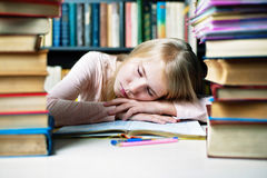 Muchacha cansada del estudiante con los libros que duerme en la tabla educación, sesión, exámenes y concepto de la escuela Fotografía de archivo libre de regalías