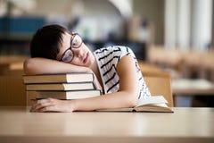 Muchacha cansada del estudiante con los vidrios que duerme en los libros imágenes de archivo libres de regalías