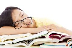 Muchacha cansada del estudiante con los vidrios que duerme en los libros Foto de archivo libre de regalías