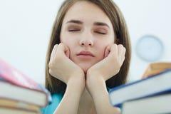 Muchacha cansada del estudiante o mujer joven con los libros y el café que duerme en biblioteca imagen de archivo