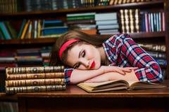 Muchacha cansada del estudiante que duerme en los libros en la biblioteca Imágenes de archivo libres de regalías