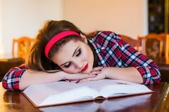 Muchacha cansada del estudiante que duerme en los libros en la biblioteca Fotos de archivo