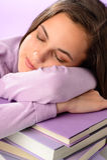 Muchacha cansada del estudiante que duerme en los libros púrpuras Foto de archivo libre de regalías