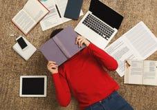Muchacha cansada del estudiante que miente en el piso con los libros y los artilugios Imágenes de archivo libres de regalías