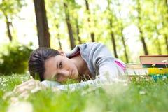 Muchacha cansada del estudiante que miente en hierba Imágenes de archivo libres de regalías