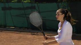 Muchacha cansada del jugador de tenis de la mujer que golpea la bola con la estafa almacen de video