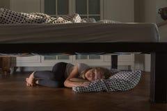 Muchacha cansada que duerme debajo de la cama con Teddy Bear Foto de archivo libre de regalías