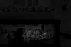 Muchacha cansada que duerme debajo de la cama con Teddy Bear Fotografía de archivo libre de regalías