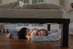 Muchacha cansada que duerme debajo de la cama con Teddy Bear Imagen de archivo