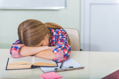 Muchacha cansada que duerme en sala de clase Foto de archivo libre de regalías
