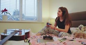 Muchacha carismática del adolescente que pasa tiempo en su dormitorio que juega en Playstation delante de la TV, muy impresionada metrajes