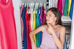 Muchacha casera del estante de la ropa del armario que piensa en el equipo Imagenes de archivo