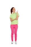 Muchacha casual con los vaqueros rosados que indican algo con el finger Foto de archivo