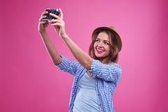 Muchacha casual exaltada que hace el selfie con una cámara de plata del vintage Fotografía de archivo libre de regalías