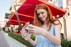 Muchacha casual joven que juega a juegos en el teléfono móvil Imágenes de archivo libres de regalías