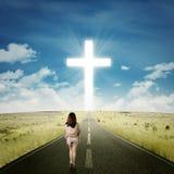 Muchacha casual que camina hacia una cruz Foto de archivo