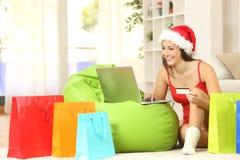 Muchacha casual que compra en línea para la Navidad fotos de archivo