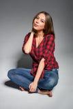 Muchacha casual que se sienta descalzo en el piso que sonríe en la cámara Imagen de archivo libre de regalías
