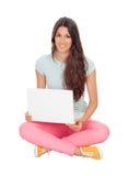 Muchacha casual que se sienta en el piso con un ordenador portátil Fotografía de archivo