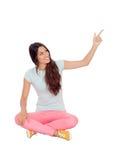 Muchacha casual que se sienta en el piso que señala algo Imagen de archivo libre de regalías