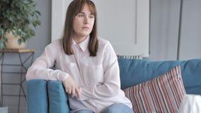 Muchacha casual que se sienta en el sofá en casa metrajes