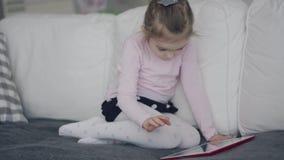 Muchacha casual que usa la tableta en el sofá metrajes