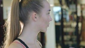 Muchacha caucásica atractiva que bebe una bebida de la sacudida de la proteína y que sonríe en el gimnasio almacen de metraje de vídeo