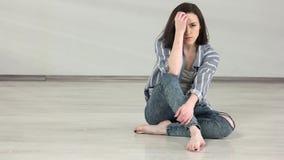 Muchacha caucásica atractiva que se sienta en el piso en estudio de la danza almacen de video