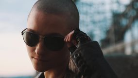 Muchacha caucásica calva del maricón andrógino con mirada de la perforación de la ceja sobre las gafas de sol almacen de video