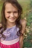 Muchacha caucásica con el pelo rizado que se sienta en hierba Foto de archivo libre de regalías
