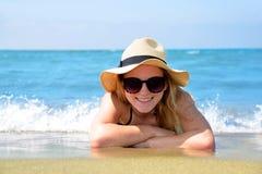 Muchacha caucásica con el sombrero que miente en la playa Imágenes de archivo libres de regalías