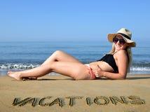 Muchacha caucásica con el sombrero que miente en la playa Imagenes de archivo