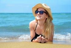 Muchacha caucásica con el sombrero que miente en la playa Foto de archivo libre de regalías
