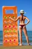 Muchacha caucásica con el sombrero y el colchón inflable en la playa Imagen de archivo libre de regalías