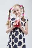 Muchacha caucásica con las coletas que se colocan en la polca Dot Dress con la taza de jugo rojo Imagen de archivo libre de regalías