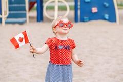 Muchacha caucásica del bebé que sostiene la bandera canadiense fotos de archivo libres de regalías