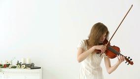 Muchacha caucásica del violinista en un fondo blanco almacen de video