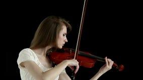 Muchacha caucásica del violinista en un fondo negro almacen de metraje de vídeo