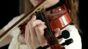 Muchacha caucásica del violinista en un fondo negro almacen de video