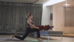 Muchacha caucásica deportiva hermosa joven que ejercita las posiciones de la yoga, asana dentro almacen de video