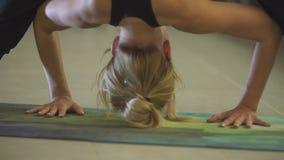 Muchacha caucásica deportiva hermosa joven que ejercita las posiciones de la yoga, asana dentro almacen de metraje de vídeo