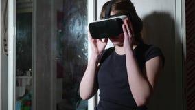 Muchacha caucásica en auriculares negros de los arreglos de la camiseta y vidrios de VR metrajes