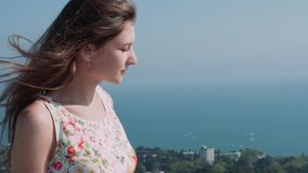 Muchacha caucásica hermosa en una terraza sobre la ciudad contra el mar almacen de video