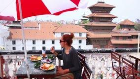 Muchacha caucásica hermosa que come el desayuno, almuerzo en el tejado, Katmandu, Nepal, almacen de metraje de vídeo